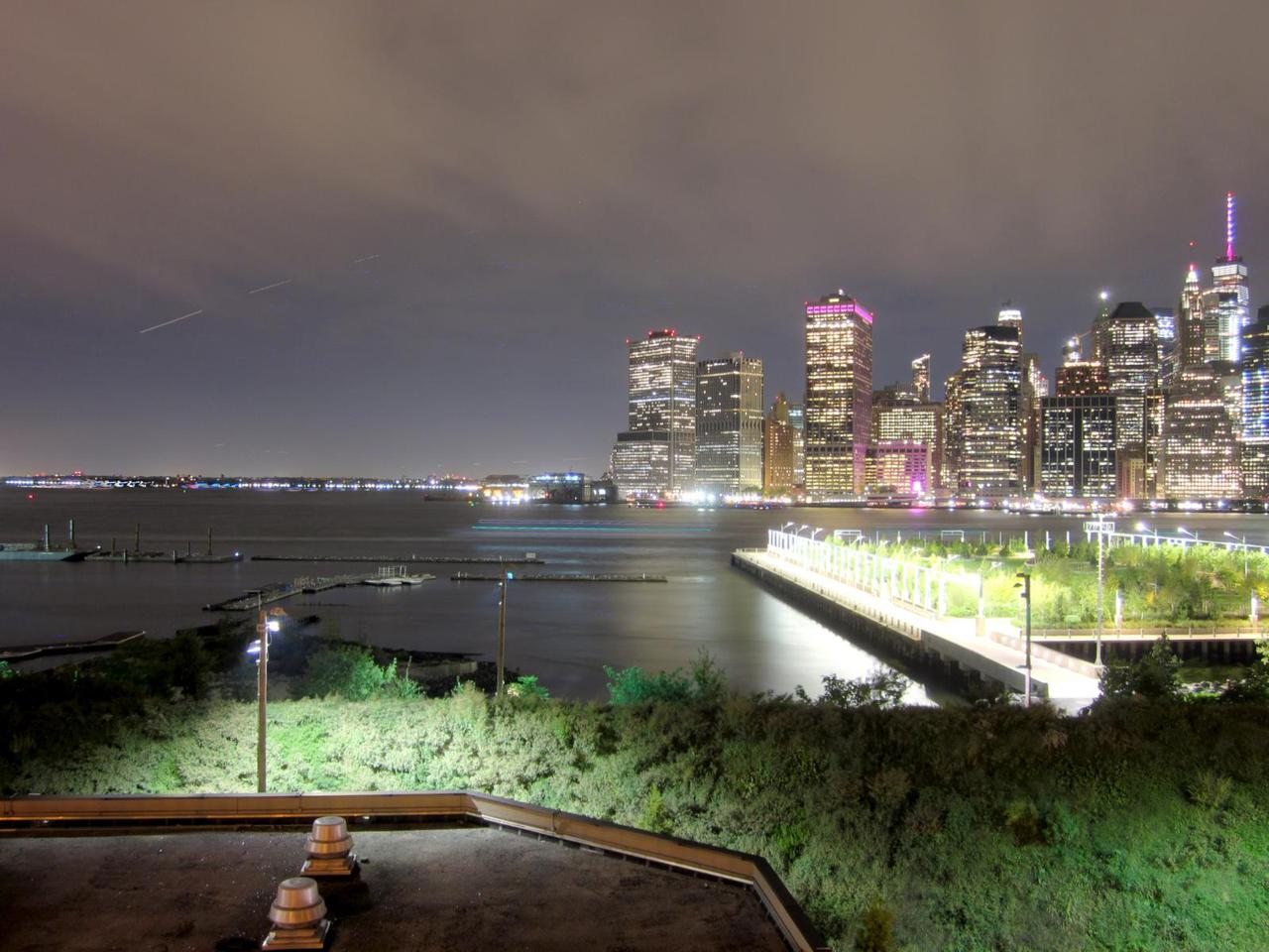 view of southern tip of manhattan at night from brooklyn