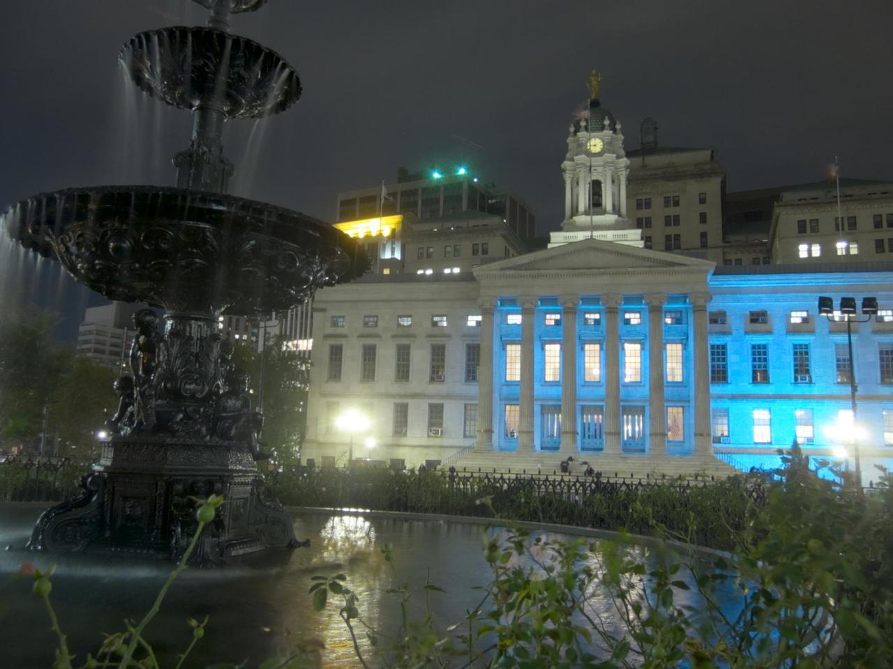 brooklyn borough hall at night, with a fountain in the foreground