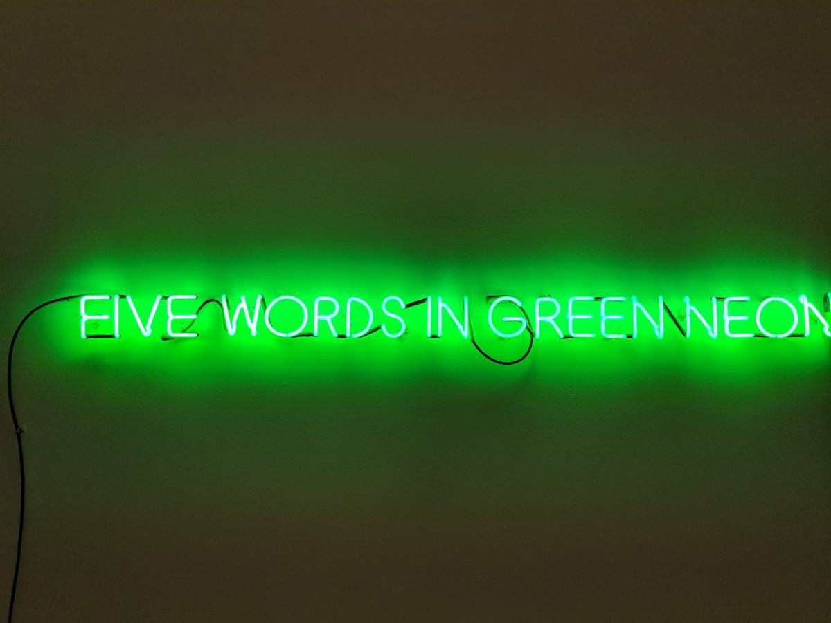 "The exact words ""Five Words in Green Neon"" are displayed with a green neon light."