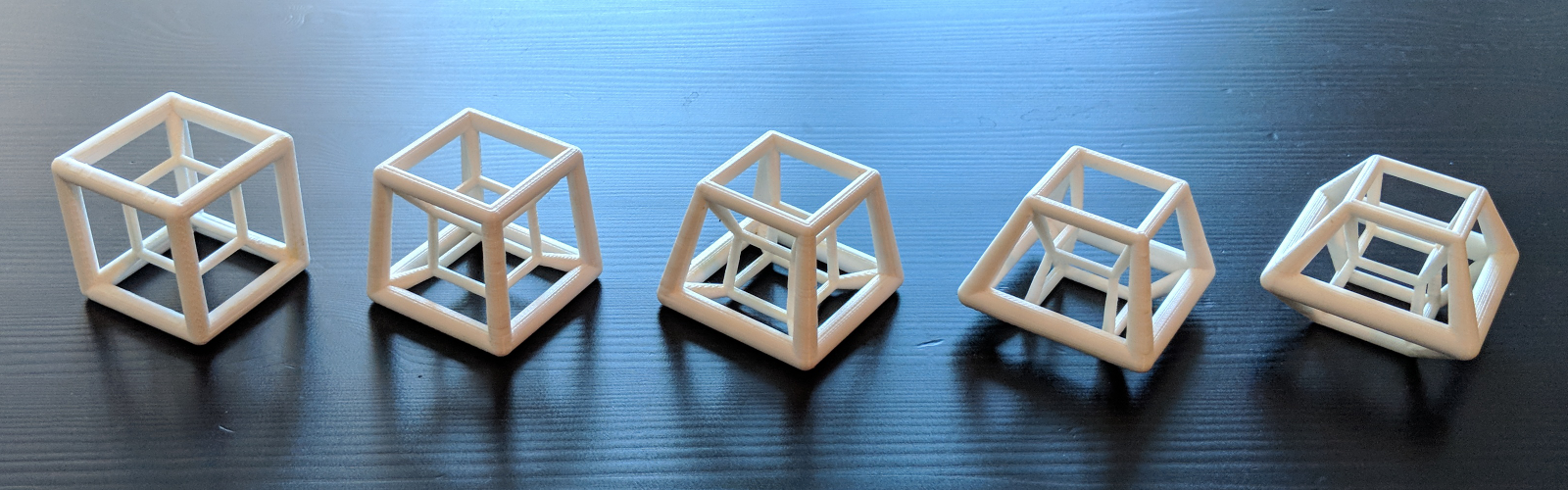 series of five printed hypercubes in a row, sitting on a wooden table.