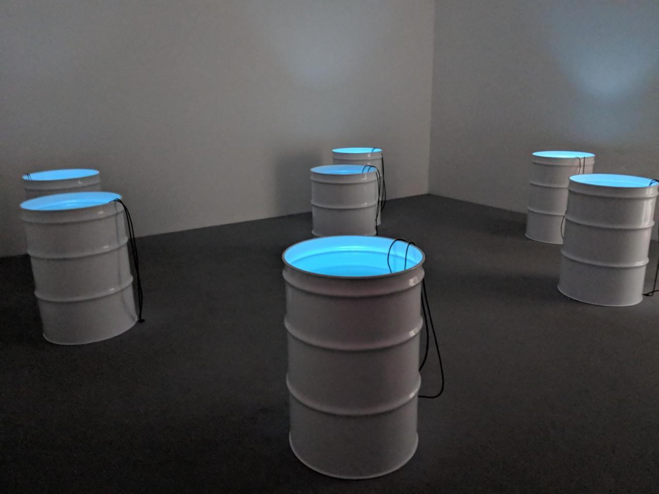 seven white oil drums with blue light and two black wires coming out of each