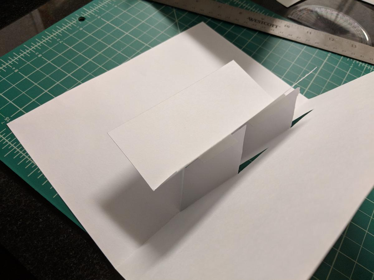 folded paper card with raised platform surface coming out of the center.