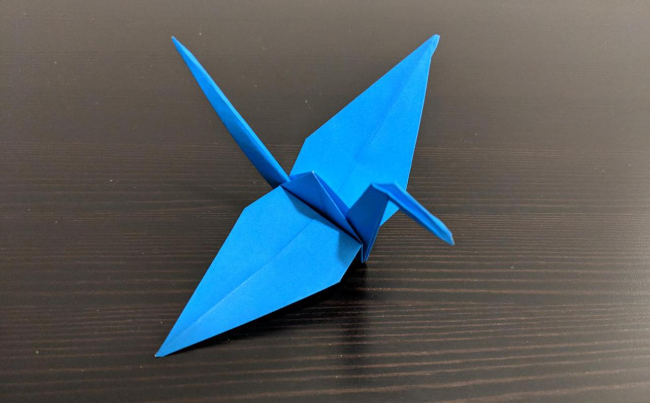 origami crane, with two wide wings a neck and head in the front and a long thin tail in the back.