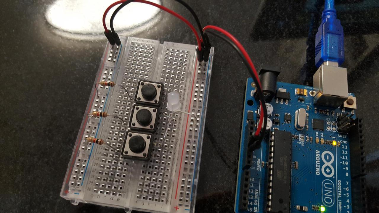 Arduino, breadboard with 3 buttons and 3 identical resistors, all connected to a 3 color LED.