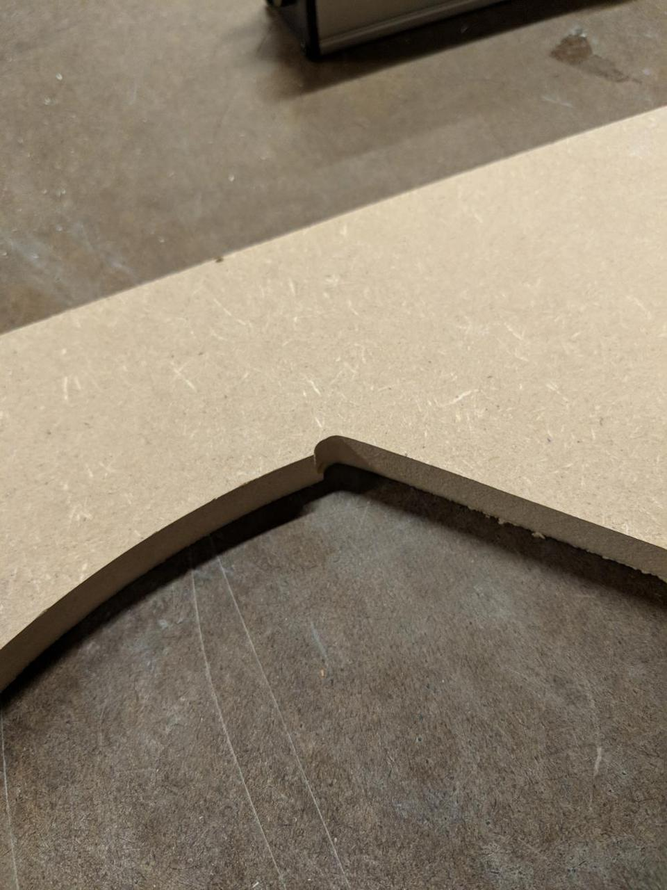 edge of piece of wood with sloppy corner, with two cut lines partially overlapped.