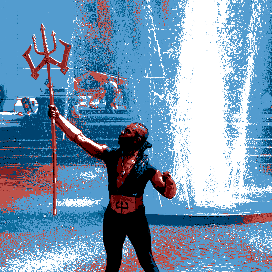 Somebody dressed as Poseidon, holding Poseidon's staff, while standing in a fountain.